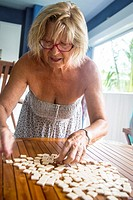 Older mature senior blond caucasian woman in her 60's , 70's playing scrabble, bananagram letters and words board game on a wood table.