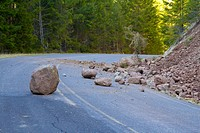 This national forest road is blocked by a land slide of rock and debris to where it is a hazard for drivers in cars.