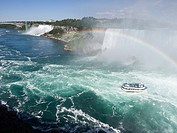 Sightseeing boat at Niagara Falls on Canadian side with rainbow.