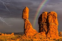 Balanced Rock Storm ANP - The golden light from the setting sun bathes Balanced Rock briefly after a heavy storm. A stormy sky and lightning can be se...
