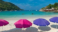 Colorful beach umbrellas on idyllic beach of Raya island, Thailand.