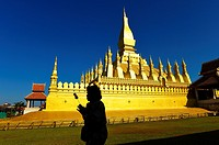 Silhouette of woman praying in Pha That Luang temple,Vientiane,Laos,Southeast Asia.