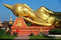 Giant gold reclining sleeping Buddha statue near Wat That Luang temple,Vientiane,Laos,Southeast Asia.
