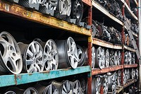 Wheel rims and car transmissions on shelves for resale.