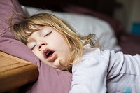 funny face expression with open mouth of blonde caucasian three years old child, sleeping on king bed.