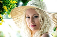 A portrait of a pretty 30 year old blond woman wearing a straw hat smiling at the camera.