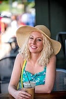A pretty 30 year old blond woman sitting at an outdoor cafe with a cold drink smiling at the camera.