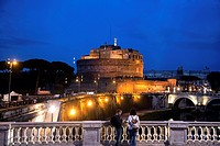 Couple of tourist watching Castel Sant'Angelo from bridge at night, Rome, Italy, Europe.