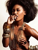 Artistic sensual beauty portrait of a young african american black woman wearing jewelry covering her topless bare body biting her finger on light stu...