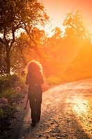 Rear view of woman walking along a path surrounded by forest at sunset.