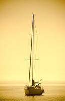 Yacht with sails down entering Oakville marina on lake Ontario.