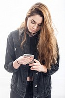 A pretty 15 year old girl texting / messaging on smartphone in the studio against a white backdrop in the Uk.