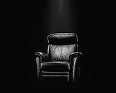 Black leather armchair in spotlight, dark background.