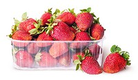 Freshly strawberries in a plastic tray and two near isolated on white background.