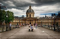 View on facade of Institut de France in Paris from Pont des Arts at cloudy day.