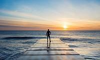 Seaton Carew, County Durham, north east England. United Kingdom. A mature jogger looks out over the North sea at sunrise.