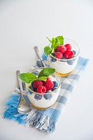 Cream with honey, blueberries, raspberries and mint leaves.