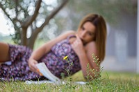 Learning in park distracted by Yellow flower focused on flower blurred student