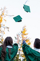 Two college students throw their caps in the air during graduation ceremonies at a university in Oregon.