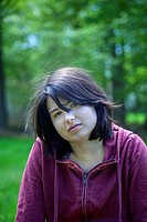 Young woman, wearing a red sweatshirt, in front of trees in a park.