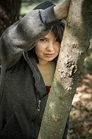 Young woman, leaning on a tree in a park, wearing a sweatshirt and hoodie.