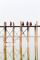 Monks crossing U Bein bridge, Amarapura's Taungmyo lake, Mandalay region, Myanmar.