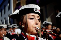 A young woman plays the trumpet at a music band wearing a traditional Spanish military hay during Easter Week celebrations in Baeza, Jaen Province, An...