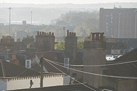 Early morning summer haze over C18th rooftops and chimney pots with tobacco factory backdrop, Hotwells, Bristol, England, UK.