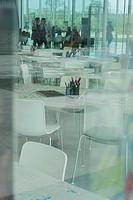 Reflective table coverings and art materials through glass in activity area of contemporary curved glass space with students, Lens, France.