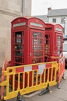 Red telephone boxes and defibrillator cordoned off with yellow and orange barriers in Monmouth market square, Wales, UK.