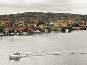 Traditional Scandinavian wooden painted houses with speed boat on the coast at Kabel near Gothenburg, Sweden.