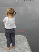 Fed up little girl with bunchies who's shoe has fallen in the water, coastal village near Gothenburg, Sweden.
