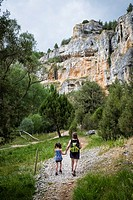 A five year old woman and a girl five years old walk along the bottom of the Río Lobos Canyon. Rocky Walls in the Canyon Lobos River Natural Park. Sor...