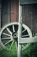 Old wagon wheel outside rural building wall. Rustic wooden nostalgia object.