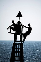 Silhouette of three youths balance on a harbour marker at the entrance to cartagena harbour in Murcia Spain.