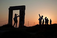 Silhouettes of the tourists at the famous Portara, unfinished door of Apollon Temple, in town center at sunset, Naxos, Cyclades Islands, Greek Islands...