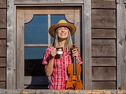 Attractive Country-girl with cup of coffee cappuccino and violin in hands laughing standing front frontal view in wild west environment. Croatia.