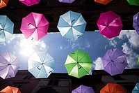 A series of umbrellas of different colors hung with a steel wire.