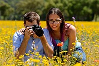 Young man and girl, photographing flowers in a field.
