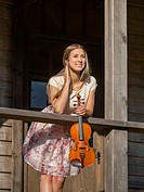 Beautiful female young woman adult teen teenager violin player violinist outdoors inclined on wooden fence porch in wild west environment. Croatia.