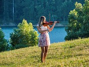 Young female musician violinist in nature near lake playing violin instrument. Croatia.
