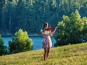 Young female musician violinist in nature near lake playing violin