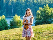 Young female musician violinist in nature near lake