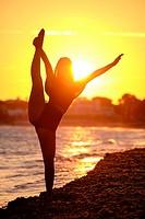 Young woman doing yoga, playa de Sa Rapita, Campos, Mallorca, balearic islands, Spain.