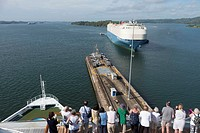 Tourists watch as a ship approaches a lock in the Panama Canal.