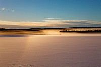 Vapors rising from a frozen lake are illuminated by the setting sun. Agnsjön, Bredbyn, Västernorrland, Sweden.