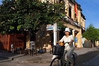 Vietnam, Quang Nam Province, Hoi An, Old Town, listed as World Heritage by UNESCO, traditional house. Bach Dang street. Vietnam. A woman on bicycle. .