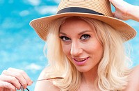 A 31 year old blond woman smiling at the camera wearing a straw hat with a swimming pool in the background.