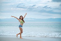 Happy hispanic woman enjoying beach walk.