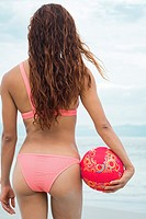 Backside of attractive woman in bikini holding a volleyball at a beach.